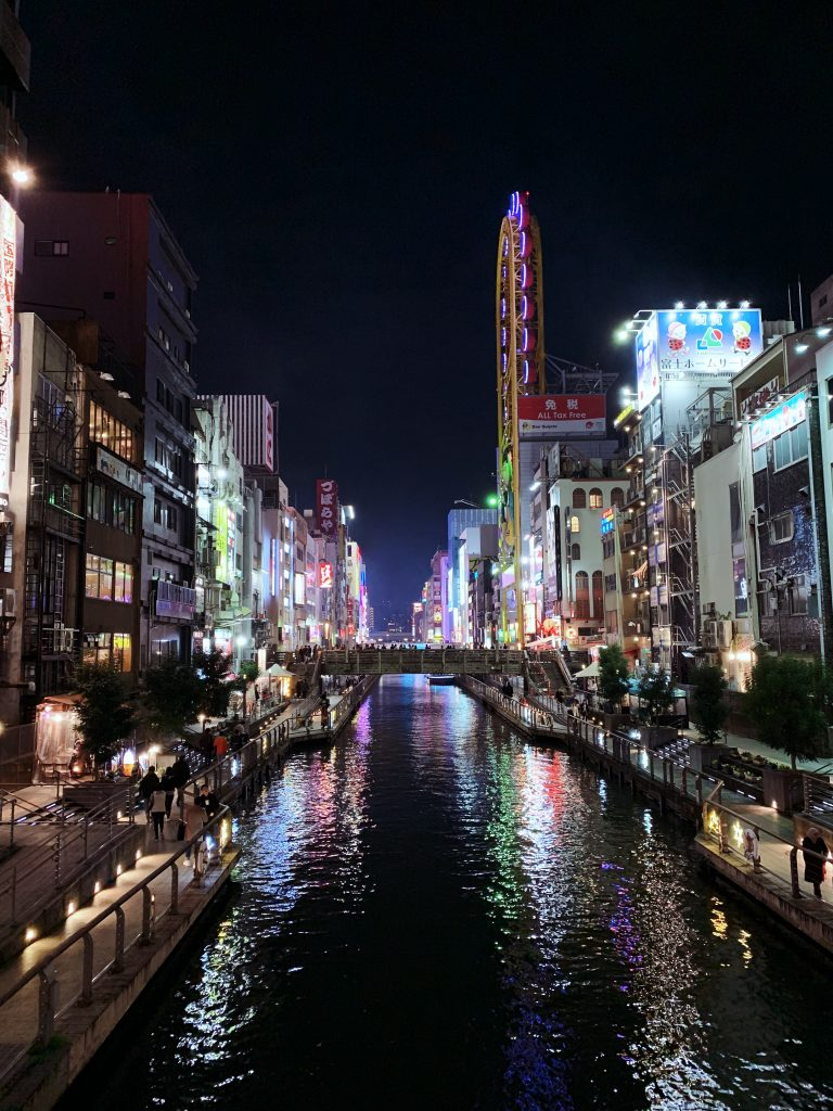 City of Osaka at night with reflection in the river running through it