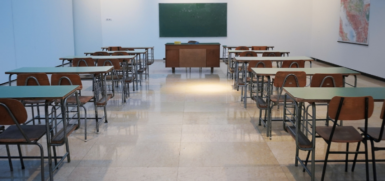 photo of an empty classroom with student and teacher desk